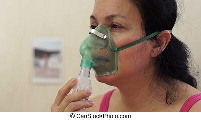 Medical Nebulizer Breathing Mask - Side shot of a woman...