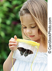 Child Capturing Butterflies - Little girl admires a...