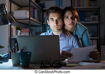 Young couple checking bills at night - Young couple using a...