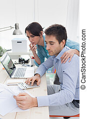Couple checking bills at home - Young affectionate couple at...