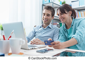 Online shopping at home - Happy young couple at home surfing...