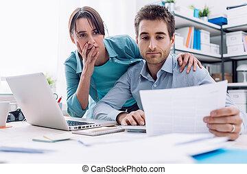Couple checking bills at home