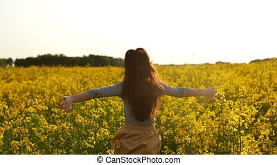 girl runs arms outstretched through a field - young...