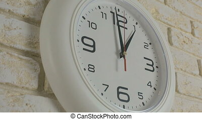 Time one hour. Timelapse. Round white clock hanging on brick...
