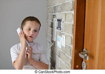 Little baby boy talking on intercom mounted on wall