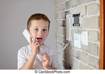 Little baby boy talking on intercom mounted on wall