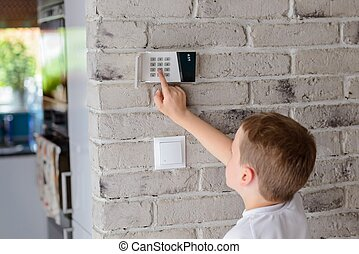 Little baby boy pushes a buttons on the alarm keypad