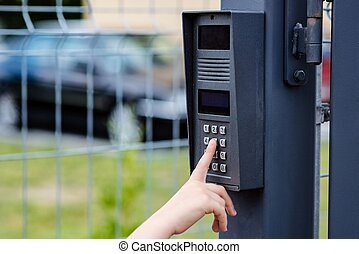 Little child boy pushes a button on the intercom mounted on...