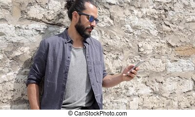 man texting message on smartphone at stone wall 3 - leisure,...