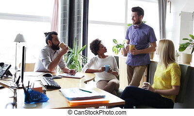happy creative team drinking coffee in office - business,...