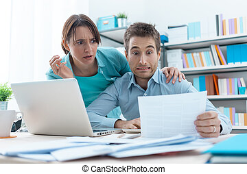 Stressed couple checking bills - Stressed young couple...