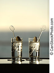 Gin - Two gin and tonics with stirrers with ocean view