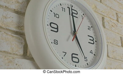 Time five hour. Timelapse. Round white clock hanging on...