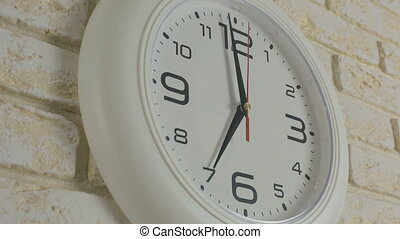 Time seven hour. Timelapse. Round white clock hanging on...