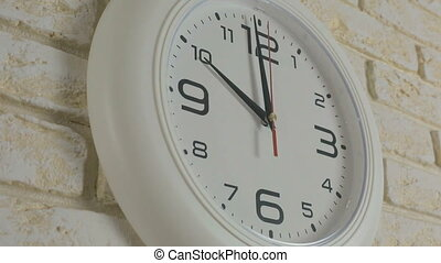 Time ten hours Timelapse Round white clock hanging on brick...