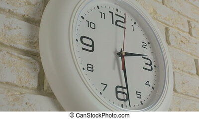 Time two hours thirty minutes. Timelapse. Round white clock hanging on brick wall.