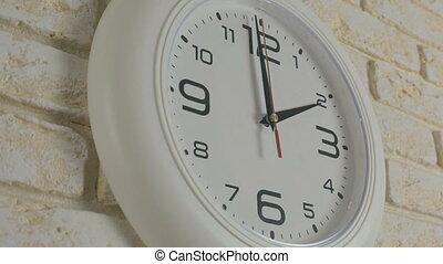 Time two hour. Timelapse. Round white clock hanging on brick wall.