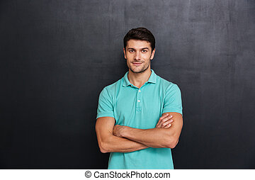 Happy young man standing with arms crossed over blackboard...
