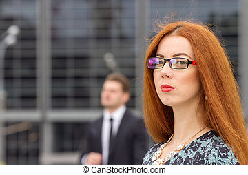 Redhair woman posing on jumping businessman background
