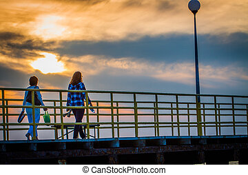 Women strolling along the pier during sunset.