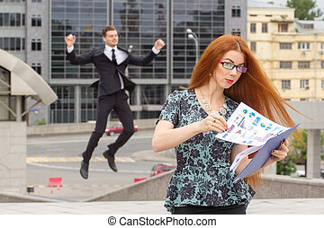 Red-haired businesswoman and businessman on background -...