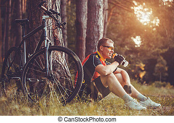 man cyclist rides in the forest on a mountain bike. - Happy...