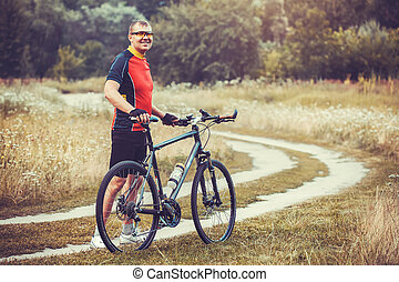 man cyclist rides in the forest on a mountain bike - Happy...