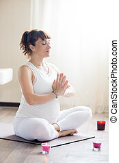 Pregnant woman meditating in yoga sukhasana pose at home -...