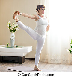 Pregnant woman doing Extended Hand to Big Toe yoga pose at...
