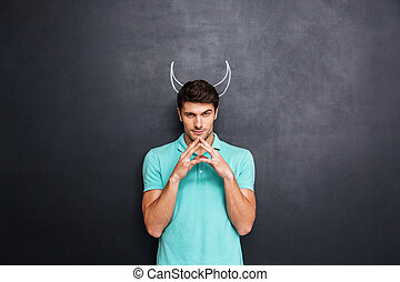 Serious man playing role of devil standing over blackboard...