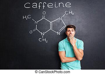Tired sleepy man yawning over blackboard with drawn caffeine molecule