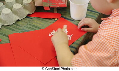 Little Boy Gluing Paper - Little boy gluing some red paper...