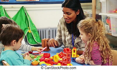 Playing building blocks at nursery - Teacher playing with...