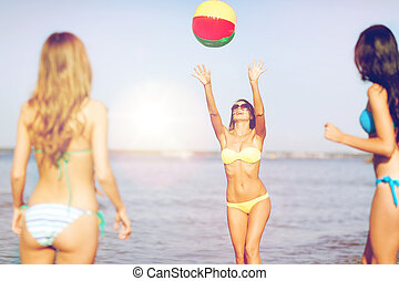 girls with ball on the beach - summer holidays, vacation and...