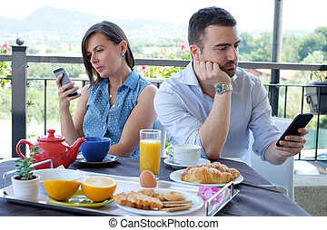 Bored couple using smartphone during breakfast time