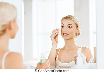 young woman with lotion washing face at bathroom - beauty,...