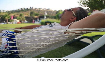 Closeup Of Relaxing Man In Hammock - Middle aged man...