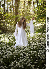 Beautiful woman in long white dress standing in a forest on a carpet of flowers
