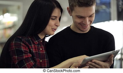 Woman embraces man by arm and together they smile and look at tablet.