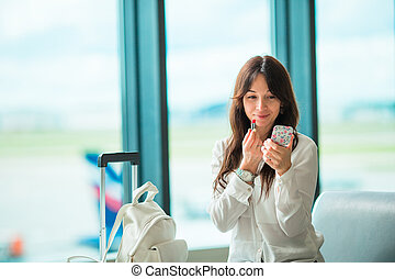 Airline passenger in an airport lounge waiting for flight aircraft and coloring lipstick. Caucasian woman with red lipstick in the waiting room