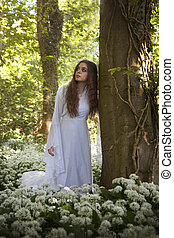 Beautiful woman wearing a long white dress leaning against a tree