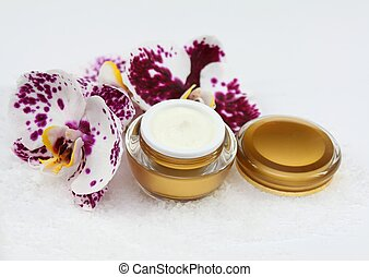 Face and body cream with orchid and sea salt on white...