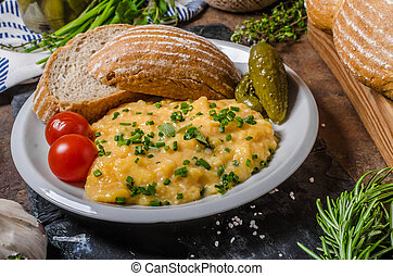 Scrambled eggs in a frying pan, lots of herbs like chive and...