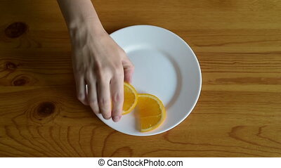 Putting segments of orange on a plate on a wooden table.