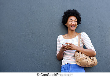 Attractive african woman smiling with mobile phone and bag -...