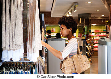 Beautiful woman looking for clothes in store - Portrait of...