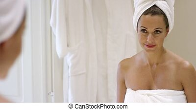 Gorgeous young woman wrapping her hair in a towel