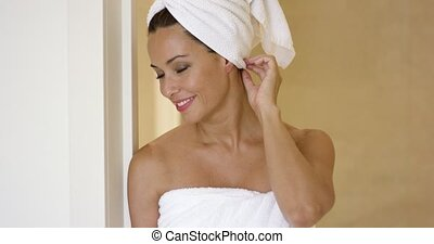 Woman wearing towel and with hair wrapped smiles over...