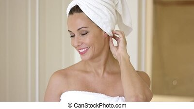 Woman wrapped in towel smiles at camera as she exits the...