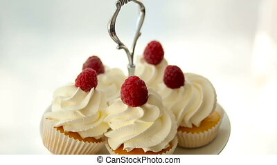 finished cupcakes with white cream and raspberries - the...